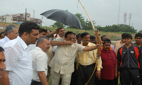 Honourable Minister inaugurating the function in the traditional way by shooting an arrow and he sco